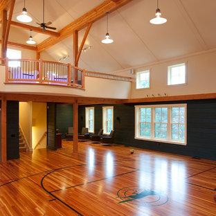 Landhausstil Fitnessraum mit Indoor-Sportplatz, schwarzer Wandfarbe und braunem Holzboden in Boston
