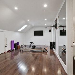 Immagine di una grande palestra multiuso classica con pareti bianche, pavimento in legno massello medio, pavimento marrone e soffitto a volta