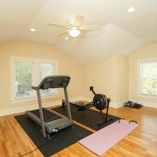 Ispirazione per una sala pesi stile americano con pareti gialle e pavimento in legno massello medio