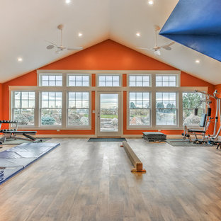 Multifunktionaler, Großer Moderner Fitnessraum mit oranger Wandfarbe und braunem Holzboden in Boise