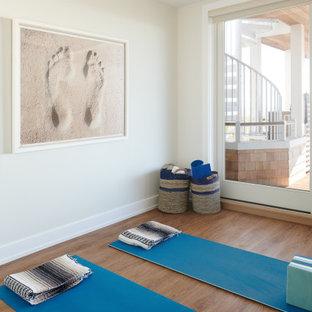 ニューヨークの中くらいのビーチスタイルのおしゃれなヨガスタジオ (白い壁、ラミネートの床、茶色い床) の写真