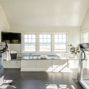 Photo of a coastal multi-use home gym in Portland Maine with white walls and dark hardwood flooring.