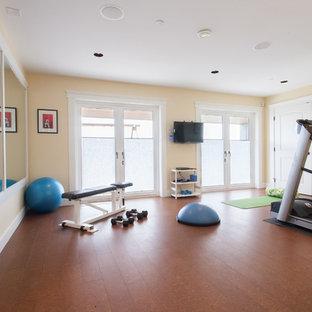 Multifunktionaler Klassischer Fitnessraum mit gelber Wandfarbe und braunem Boden in Vancouver