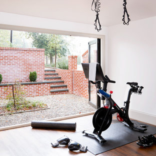 Inspiration for a transitional dark wood floor and brown floor home gym remodel in Other with white walls