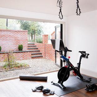 Exemple d'une salle de sport chic avec un mur blanc, un sol en bois foncé et un sol marron.