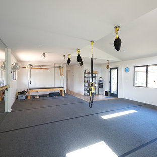 This is an example of a mid-sized modern multipurpose gym in Austin with white walls and grey floor.