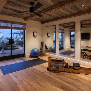 Ejemplo de estudio de yoga grande con paredes blancas y suelo de madera en tonos medios