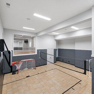 Idee per un ampio campo sportivo coperto tradizionale con pareti bianche, pavimento in vinile e pavimento marrone
