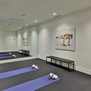 Immagine di un piccolo studio yoga minimalista con pareti bianche e pavimento grigio