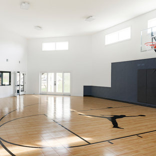 Example of a large trendy laminate floor and brown floor indoor sport court design in Minneapolis with white walls