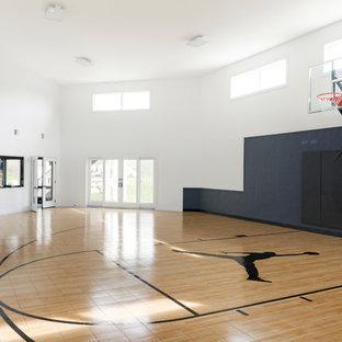 Großer Moderner Fitnessraum mit Indoor-Sportplatz, weißer Wandfarbe, Laminat und braunem Boden in Minneapolis