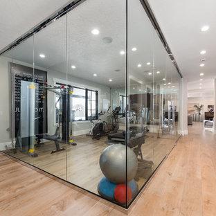 Réalisation d'une salle de musculation tradition de taille moyenne avec un mur beige, un sol en bois clair et un sol beige.