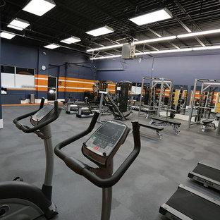 Idée de décoration pour une grand salle de musculation avec un mur bleu.