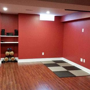 トロントの中くらいのコンテンポラリースタイルのおしゃれな多目的ジム (赤い壁、無垢フローリング、茶色い床) の写真