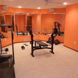 Immagine di una sala pesi classica di medie dimensioni con pareti arancioni, moquette e pavimento beige