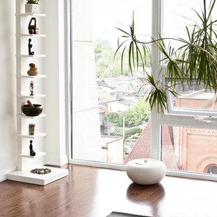 Immagine di uno studio yoga tropicale di medie dimensioni con pareti bianche e pavimento in legno massello medio