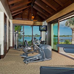 Immagine di una grande palestra multiuso tropicale con moquette, pareti bianche e pavimento beige
