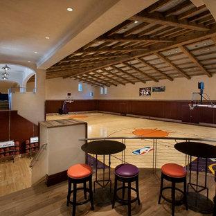 Geräumiger Mediterraner Fitnessraum mit Indoor-Sportplatz, beiger Wandfarbe und hellem Holzboden in Phoenix