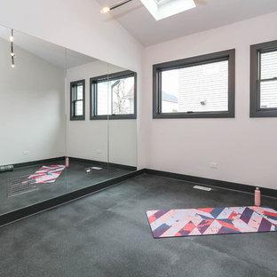 Immagine di uno studio yoga country di medie dimensioni con pareti bianche, pavimento in vinile e pavimento nero