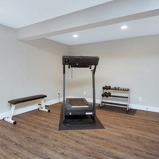 Idee per una sala pesi classica di medie dimensioni con pareti grigie, pavimento in legno massello medio e pavimento marrone