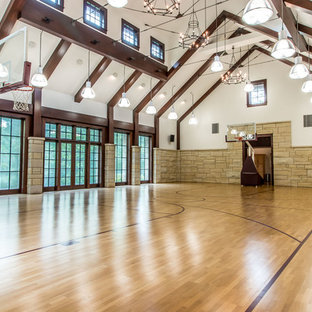 Design ideas for a traditional indoor sports court in Detroit with white walls, medium hardwood flooring and brown floors.
