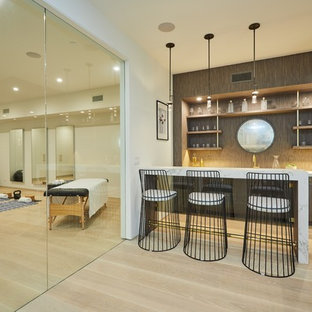 Photo of a mid-sized contemporary multipurpose gym in Los Angeles with white walls, light hardwood floors and beige floor.