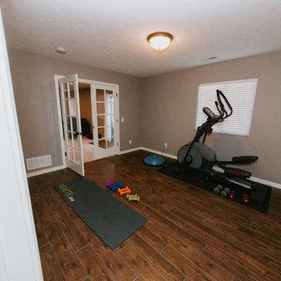 Idee per una palestra multiuso chic di medie dimensioni con pareti grigie, pavimento in legno massello medio e pavimento marrone