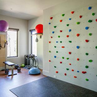Inspiration för moderna hemmagym, med vita väggar och brunt golv