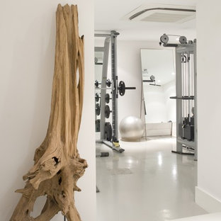 Photo of a contemporary home weight room in London with white walls and white floors.