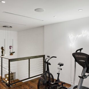 Contemporary home gym in New York with white walls and dark hardwood floors.