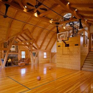 Immagine di un ampio campo sportivo coperto country con pavimento in legno massello medio e pareti marroni