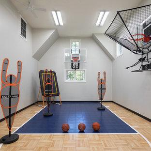 Idee per un campo sportivo coperto country di medie dimensioni con pareti bianche, pavimento in laminato e pavimento marrone