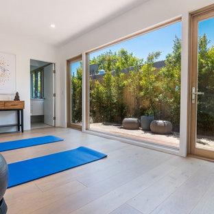 Foto di uno studio yoga moderno di medie dimensioni con pareti bianche, pavimento in legno massello medio e pavimento marrone