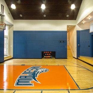 Aménagement d'un grand terrain de sport intérieur classique avec un mur bleu et un sol en bois clair.