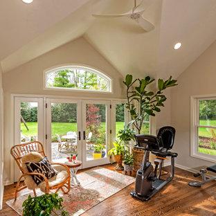 Esempio di una palestra multiuso classica di medie dimensioni con pareti beige, pavimento in legno massello medio e pavimento marrone