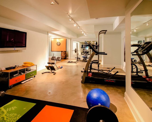 example of a trendy concrete floor and orange floor multiuse home gym design in atlanta