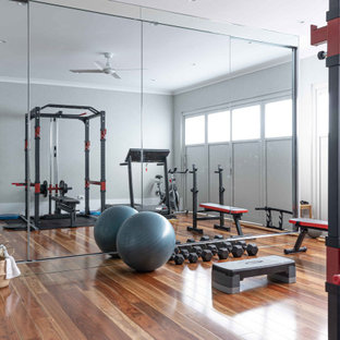 Design ideas for a large contemporary multipurpose gym in Sydney with white walls, medium hardwood floors and brown floor.
