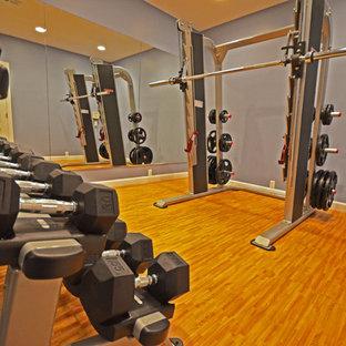 Idee per una sala pesi chic di medie dimensioni con pareti blu, pavimento in bambù e pavimento marrone