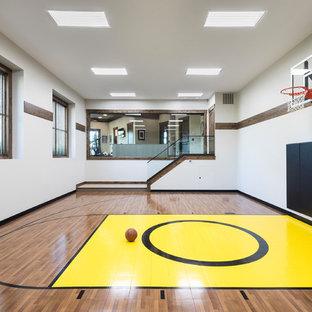 Esempio di un campo sportivo coperto stile rurale con pareti bianche, pavimento in legno massello medio e pavimento marrone