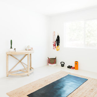 Immagine di uno studio yoga stile americano di medie dimensioni con pareti bianche, pavimento in cemento e pavimento bianco