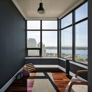 Foto på ett litet funkis hemmagym, med svarta väggar, mörkt trägolv och brunt golv
