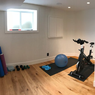 Inspiration for a mid-sized modern medium tone wood floor home gym remodel in Calgary with white walls