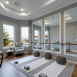 Diseño de estudio de yoga tradicional renovado con paredes grises, suelo de madera en tonos medios y suelo marrón