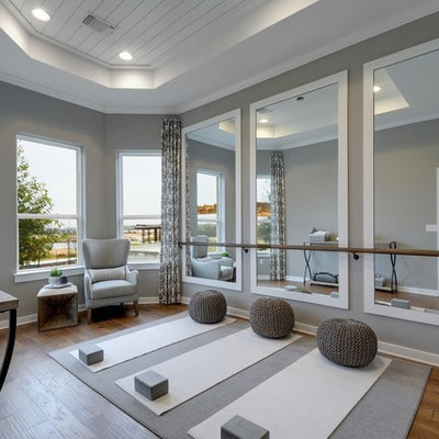 Example of a transitional medium tone wood floor and brown floor home yoga studio design in Jacksonville with gray walls