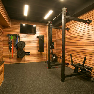 Diseño de gimnasio multiusos, contemporáneo, de tamaño medio, con paredes marrones y suelo negro