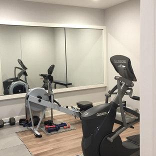 Foto di una piccola sala pesi country con pareti grigie, parquet chiaro e pavimento marrone