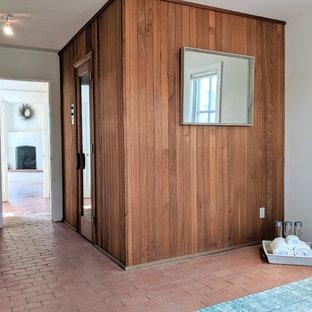 Foto di uno studio yoga american style di medie dimensioni con pavimento in mattoni, pavimento marrone e pareti beige