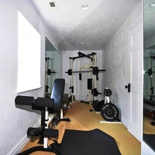 Immagine di una sala pesi mediterranea di medie dimensioni con pareti grigie e moquette