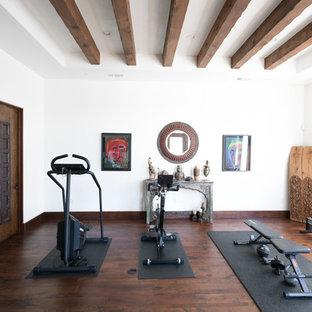 Multifunktionaler Mediterraner Fitnessraum mit dunklem Holzboden, weißer Wandfarbe und braunem Boden in Austin
