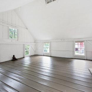 Großer Country Yogaraum mit weißer Wandfarbe, gebeiztem Holzboden und grauem Boden in New York
